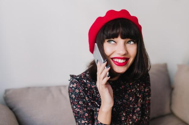 Attraktives brünettes mädchen mit roten lippen in den weinlesekleidern, die mit freund per telefon sprechen und lächeln. charmante junge frau im französischen outfit, die am sofa sitzt und freund hört, iphone hält