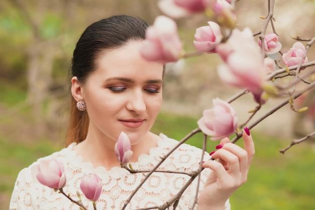 Attraktives brünettes model mit nacktem make-up, das eine spitzenbluse trägt und in der nähe der blühenden magnolienblumen posiert