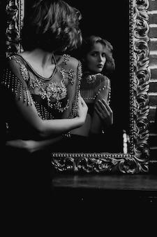 Attraktives brünettes model trägt bh und schaut in den spiegel. schwarzweißfoto