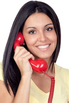 Attraktives brunettemädchen, das mit dem roten telefon lokalisiert auf weißem hintergrund benennt