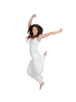 Attraktives brunettemädchen gekleidet im weißen springen