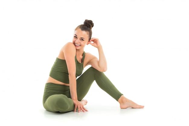 Attraktives brunettemädchen in einer grünen sportklage tut yoga