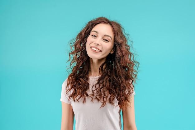 Attraktives brunettemädchen mit dem lockigen haar und einem glücklichen freundlichen lächeln