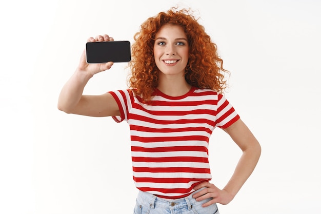 Attraktives, charismatisches ingwermädchen, lockige frisur, blaue augen, halten die hand taille, die das horizontale spielpromo des smartphones zeigt, das allgemein lächelt, rät zur coolen app-nutzung