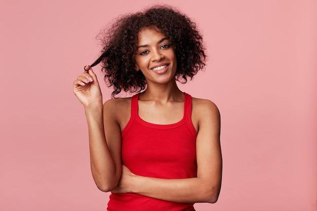 Attraktives charmantes freudiges afroamerikanisches mädchen, das wundervoll aussieht, spielt wunderbar mit lockigem dunklem haar, mit afro-frisur, zartem lächeln, rotem unterhemd tragend, isoliert