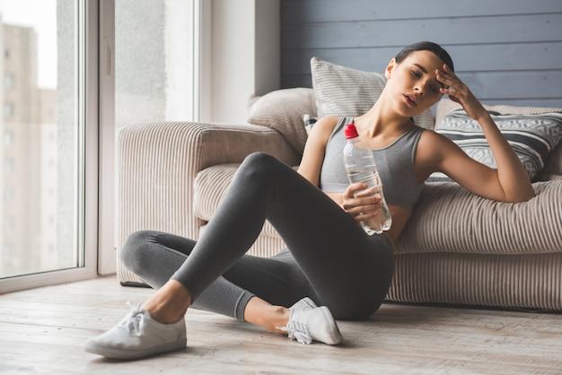 Attraktives dünnes mädchen in der sportkleidung fühlt sich müde.