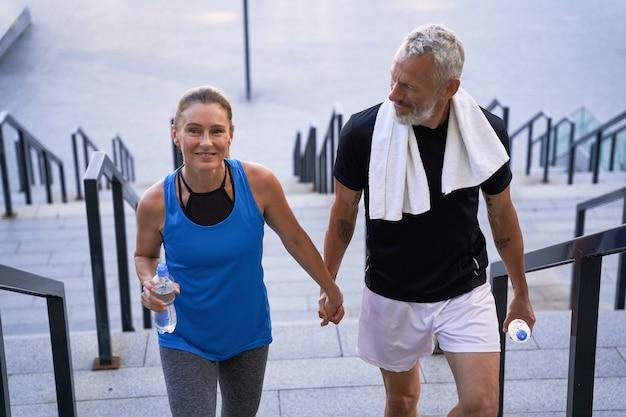 Attraktives ehepaar mittleren alters, sportlicher mann und frau, die beim gehen glücklich händchen haltend aussehen