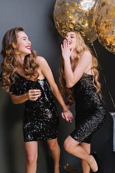 Attraktives europäisches mädchen mit glänzendem haar, das mit schwester auf neujahrsparty herumalbert. innenfoto des prächtigen blonden weiblichen modells, das hände mit freund, mit luftballons hält.