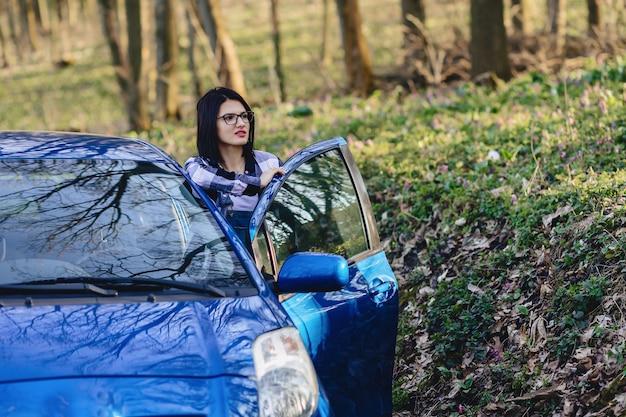 Attraktives fahrermädchen schaut aus der offenen tür des autos heraus