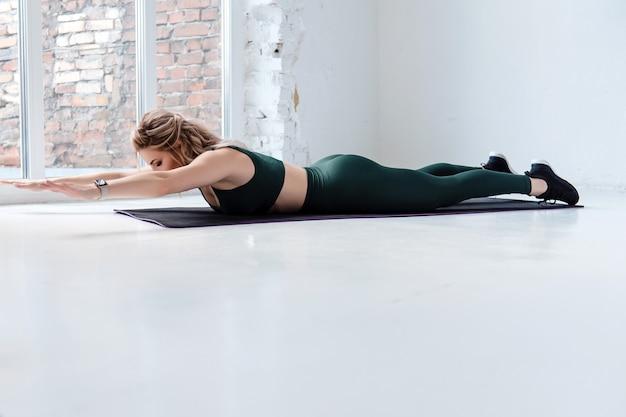 Attraktives fitness-mädchen in sport-bh und leggings auf dem bauch liegend