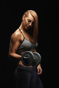 Attraktives fitnessmodel mit hanteln, die auf dunklem hintergrund in sportbekleidung posieren