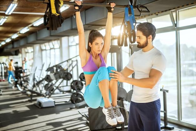 Attraktives, fokussiertes, motiviertes, aktives, sportliches mädchen, das ein bauchmuskeltraining mit erhobenen beinen durchführt, während es die stange oben und den personal trainer neben sich hält und sie im sonnigen fitnessstudio unterstützt.