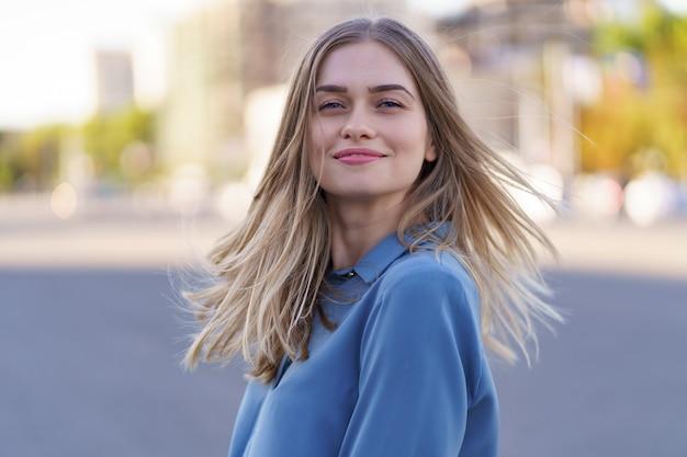 Attraktives fröhliches blondes mädchen mit fliegenden langen haaren, die lachend in der stadt lächeln