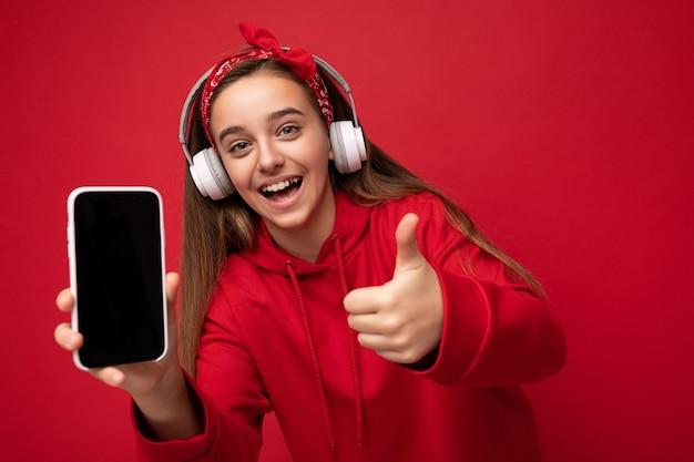 Attraktives fröhliches lächelndes brünettes mädchen mit rotem hoodie isoliert auf rotem hintergrund hält und