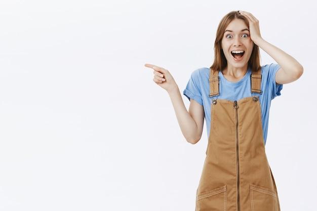 Attraktives fröhliches mädchen, das finger links auf logo zeigt, das beeindruckt aussieht