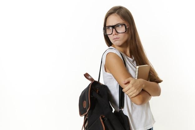 Attraktives frustriertes college-mädchen mit rucksack und lehrbuch, verärgert über nicht bestandene prüfungen, viele hausaufgaben