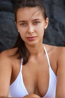 Attraktives gebräuntes junges weibliches touristenmodell trägt weiße badebekleidung