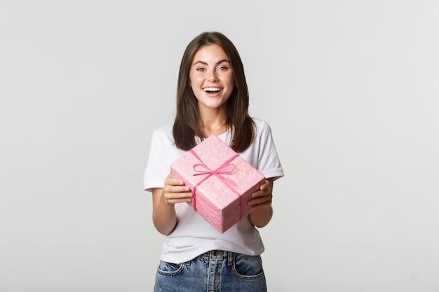 Attraktives glückliches brünettes mädchen, das geburtstagsgeschenk hält und fröhlich lächelt.