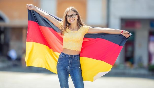 Attraktives glückliches junges mädchen mit der deutschland-flagge.