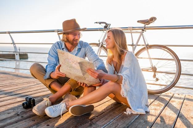 Attraktives glückliches lächelndes paar, das im sommer auf dem seeweg auf fahrrädern, mann und frau mit blondem haar boho-hipster-art-mode reist, die spaß zusammen haben und in kartenbesichtigung schauen