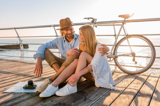 Attraktives glückliches lächelndes paar, das im sommer auf dem seeweg auf fahrrädern reist