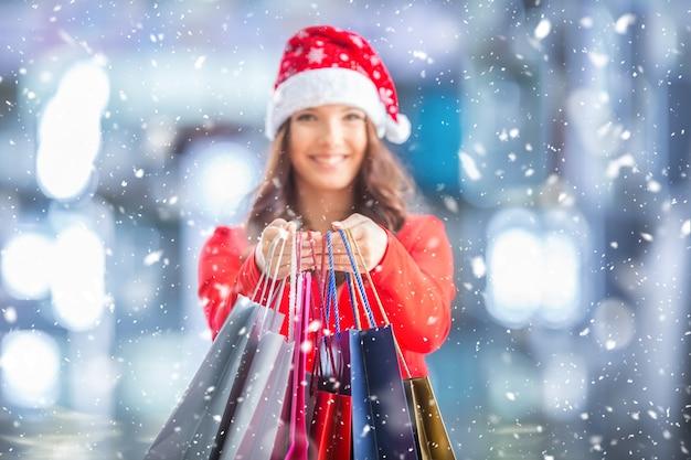 Attraktives glückliches mädchen mit kreditkarte und einkaufstüten in weihnachtsmütze snowy-atmosphäre