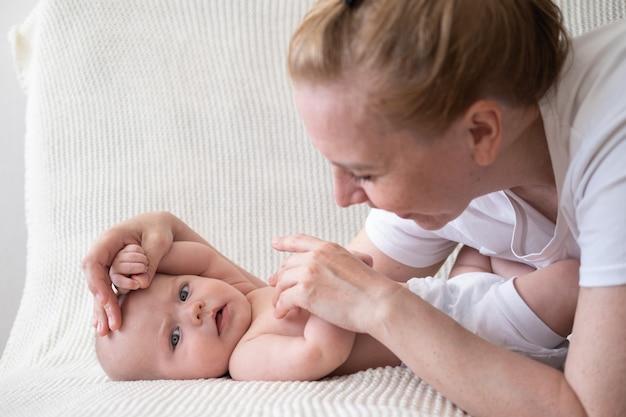 Attraktives glückliches mutterspiel mit kleinen jungenhänden. massage.