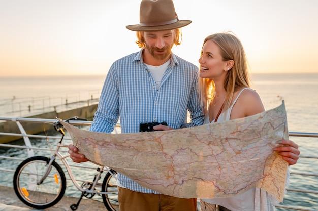 Attraktives glückliches paar, das im sommer auf fahrrädern, mann und frau mit blondem haar boho-hipster-art-mode reist, die spaß zusammen haben und in kartenbesichtigung schauen
