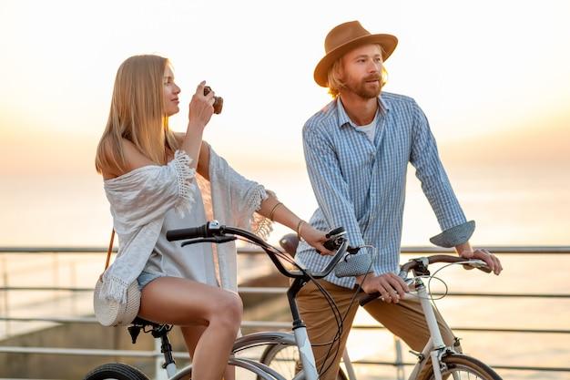 Attraktives glückliches paar, das im sommer auf fahrrädern, mann und frau mit blondem haar im boho-hipster-stil unterwegs ist und spaß zusammen hat