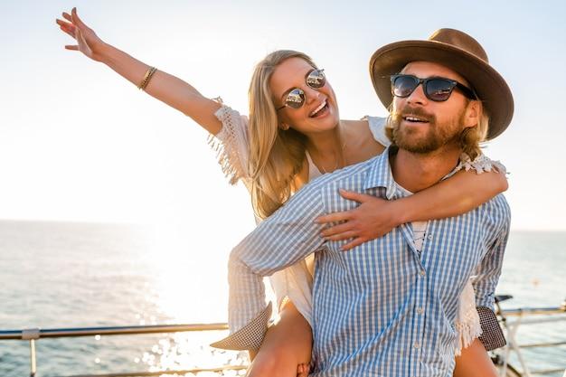Attraktives glückliches paar, das lachend im sommer auf dem seeweg lacht, mann und frau, die sonnenbrille tragen