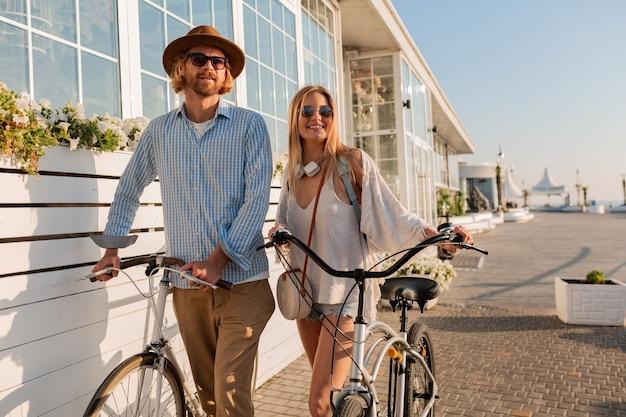 Attraktives glückliches paar von freunden, die im sommer auf fahrrädern, mann und frau mit blonden haaren reisen