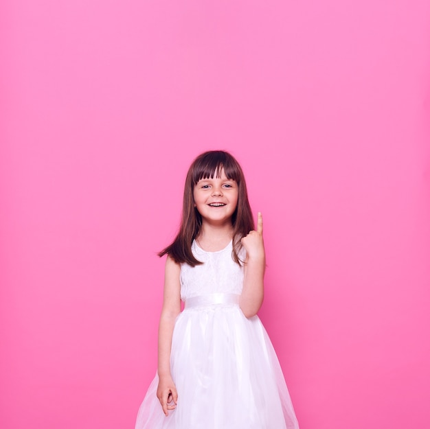 Attraktives glückliches positives kleines kind, das schönes weißes kleid trägt, das oben mit finger zeigt und front lokal über rosa wand betrachtet