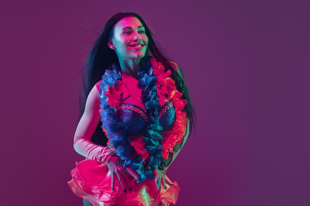 Attraktives hawaiianisches brünettes modell auf lila studiowand im neonlicht