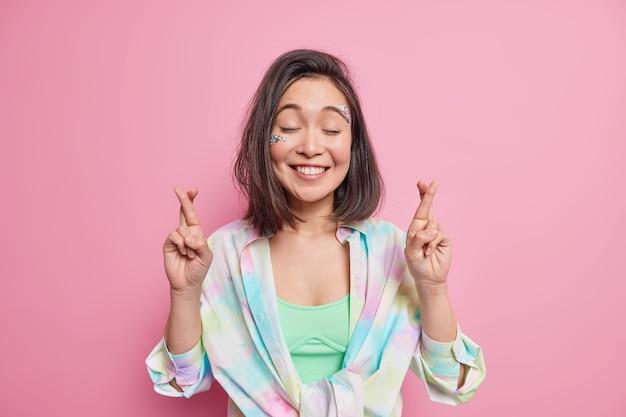 Attraktives hoffnungsvolles asiatisches mädchen hofft auf viel glück hält die daumen, schließt die augen und erwartet positive nachrichten, lächelt fröhlich trägt ein buntes hemd isoliert über rosafarbener wand gebetskonzept