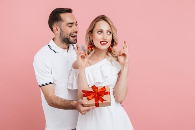 Attraktives hübsches junges verliebtes paar, das isoliert über rosa zusammensteht, geschenke gibt, die daumen für viel glück hält und das ereignis feiert