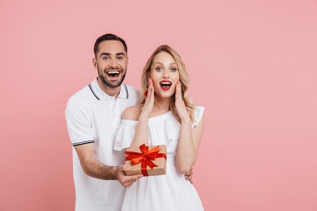 Attraktives hübsches junges verliebtes paar, das zusammen isoliert über rosa steht, geschenke gibt, ereignis feiert