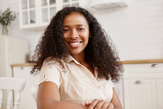 Attraktives hübsches mädchen afroamerikanischer herkunft, das gute positive gefühle ausdrückt, gegen stilvolles kücheninterieur sitzt und ein zahniges strahlendes lächeln hat. ethnizität und schönheitskonzept