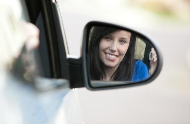 Attraktives jugendlich mädchen, das in ihrem auto hält schlüssel sitzt