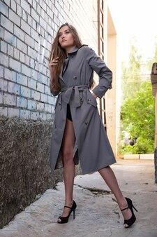 Attraktives junges asiatisches model im grauen trenchcoat, das draußen in der nähe der wand steht