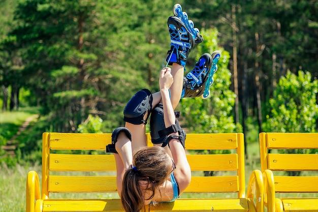 Attraktives junges, athletisches, sexy brünettes teenager-mädchen in kurzen rosa shorts und blauem oberteil mit schutz-ellbogenschützern und knieschützern rollschuhees ruht und liegt auf einer bank im sommerpark