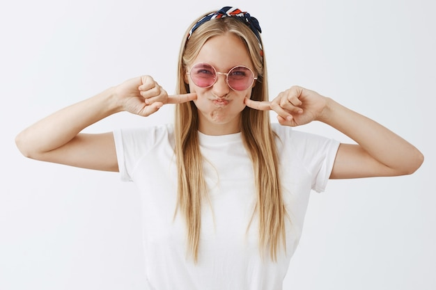 Attraktives junges blondes mädchen, das gegen die weiße wand aufwirft