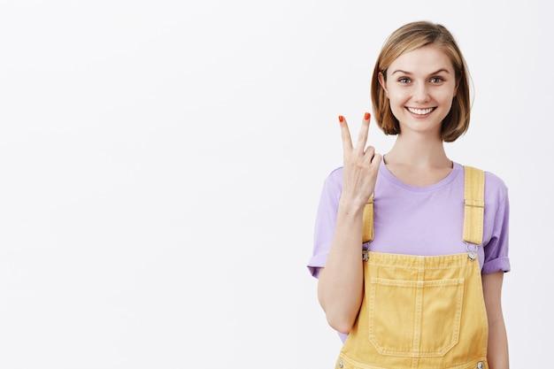 Attraktives junges blondes mädchen, das nummer zwei zeigt