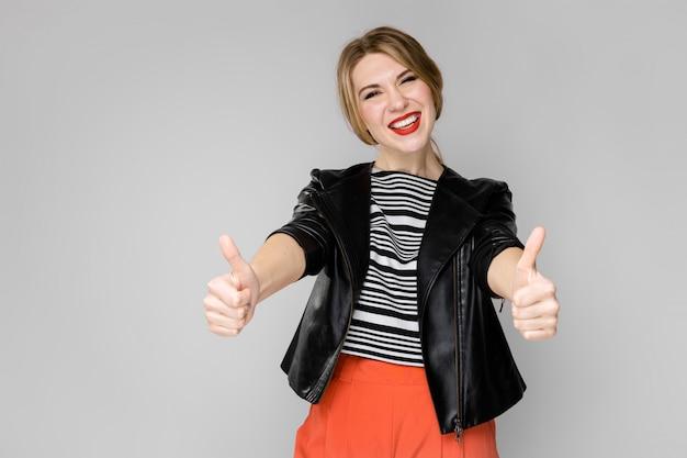 Attraktives junges blondes mädchen in der gestreiften bluse und in lederjacke lächelnd, lachend mit den daumen, die oben auf grau stehen
