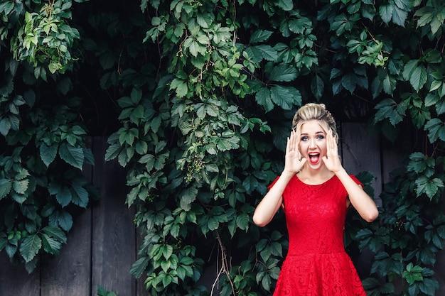 Attraktives junges blondes mädchen in einem roten kleid schreit laut vor dem hintergrund eines wilden weinbergs.