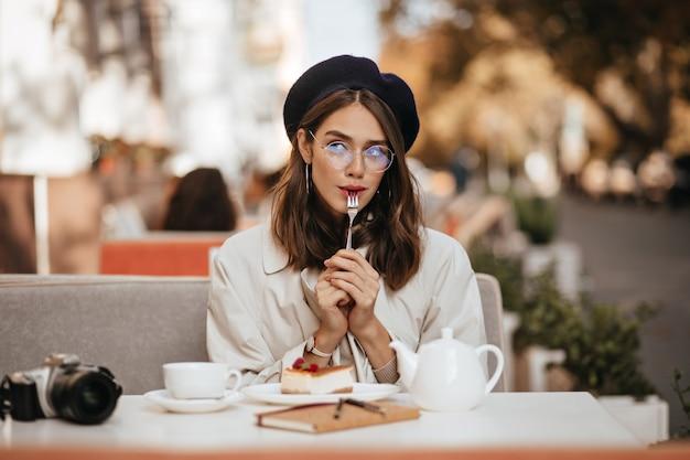 Attraktives junges braunhaariges mädchen mit brille, vintage-barett und beigem trenchcoat, chillen auf der terrasse des stadtcafés, käsekuchen und tee essen, über etwas nachdenken