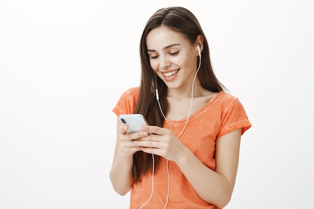 Attraktives junges brünettes mädchen, das musik in den kopfhörern hört und handy hält