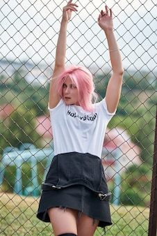 Attraktives junges fitnessmädchen, das sich auf zaun stützt und draußen steht. pinkes haar.
