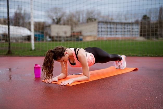 Attraktives junges fitnessmädchen, das yoga planking auf der orange matte außerhalb nahe dem fußballfeld tut.