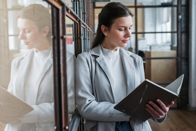 Attraktives junges geschäftsfraulesetagebuch im büro