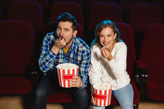 Attraktives junges kaukasisches paar, das einen film in einem kino, haus oder kino sieht.